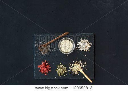 Superfoods on black chalkboard background: goji berries, chia, mung beans, buckwheat, quinoa, sunflo