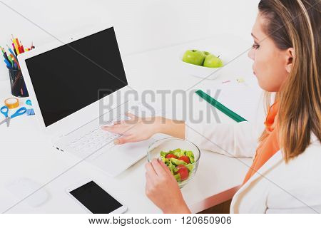 Young businesswoman with salad bowl working on laptop