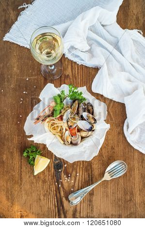 Seafood pasta. Spaghetti with clams and shrimps in bowl, glass of white wine over rustic wood backgr