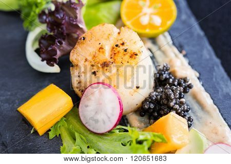 Pan Seared Scallops With Salad, Avocado, Radish, Mango And Black Caviar On A Stone Plate, Close Up