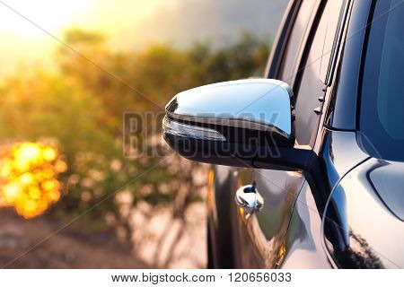 Black car side mirror with sun light effect.