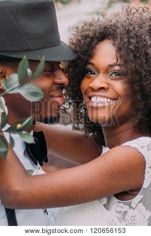 Lovely stylish black newlyweds happily smiling close up