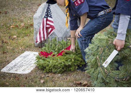 SUCCASUNNA, NJ-DEC 12, 2015: A Cub Scout from Troop 163 places a wreath on a veterans grave in the cemeteries of the First Presbyterian and United Methodist churches for 2015 Wreaths Across America.