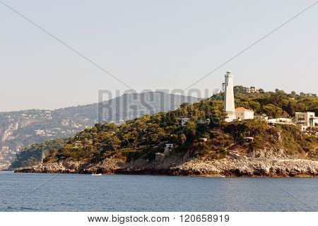 Color DSLR stock landscape image of lighthouse and homes along the Mediterranean coast of the French Riviera. Horizontal with copy space for text