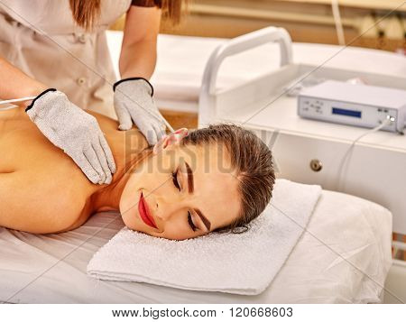 Young woman  with closed eyes lying on stomach receiving electric massage at beauty salon. Beautician wearing electricity gloves. In room is device for hardware cosmetology.