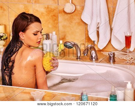 Young woman take bubble  bath at home. Woman washing her shoulder.