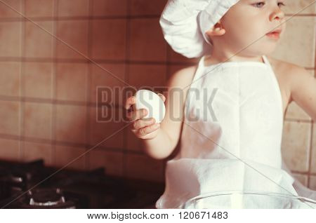 Little Boy Cook Play Dough On The Table In An Apron And Chef's Hat. The Idea For Your Advertising