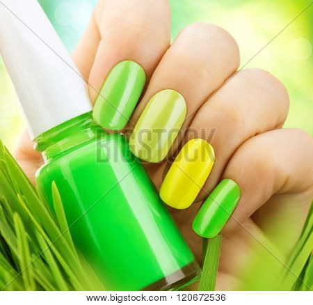 Spring green manicure. Fresh Nature trendy green nails. Beautiful nail polish with grass. Green and yellow colors Eco Nail art manicure. Bottle of Nail Polish. Fashion Beauty hands. Stylish Nailpolish