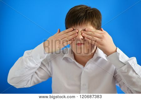 Surprised boy closes the eyes with hands