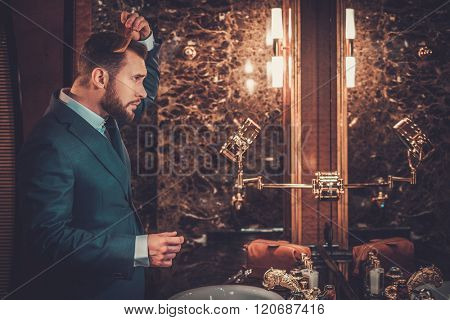 Confident well-dressed man combing hair in luxury bathroom interior.