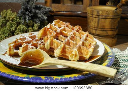 Handmade fresh belgian waffles with sugar powder and caramel syrop on rural wooden background