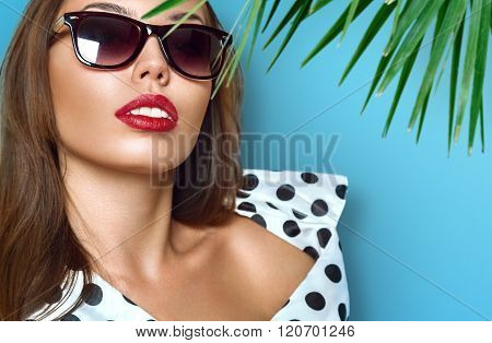 Portrait of young beautiful woman in sun glasses with perfect tanned skin
