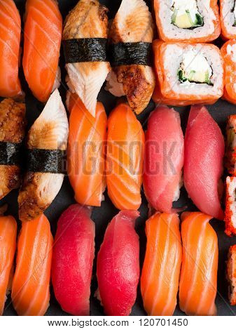 Various kinds of sushi served on black stone. Sushi Set sashimi and sushi rolls, closeup top view