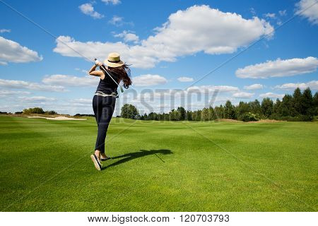 portrait of young female golf player, back view