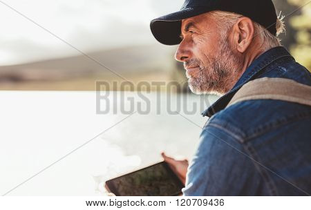 Mature Man Wearing Cap Sitting At A Lake And Looking At A View