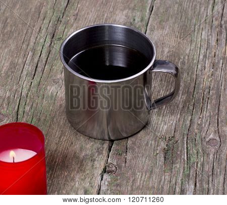 Coffee In A Steel Mug And The Burning Red Candle