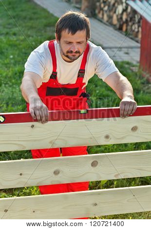 Man Building New Wooden Fence