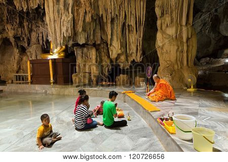 KANCHANABURI, THAILAND, JANUARY 19, 2016 : A thai family is praying and meditating with a Buddhist monk in the Wat Tham Pu Wa cave temple in Kanchanaburi, Thailand