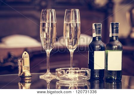 Champagne, glasses, antique keys. Luxury hotel apartment, room service concept. Vintage, retro.