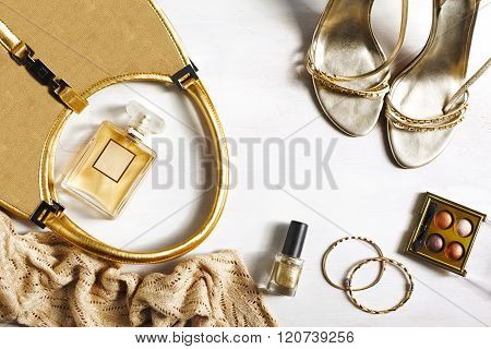 Women's set of fashion accessories in golden color on wooden background: shoes handbag perfume and cosmetics.
