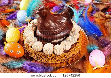 a mona de pascua, a cake eaten in Spain on Easter Monday, topped with a chocolate chicken, on a rustic wooden surface full of decorated eggs and feathers of different colors