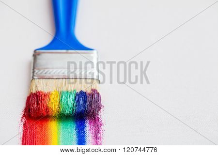 Paint Brush Closeup And Multicolor Rainbow Brush Strokes On White Canvas