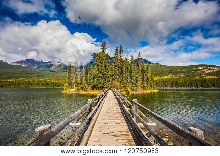 Jasper National Park, Pyramid Lake. Cold sunny morning. The picturesque little island in the middle of the lake and the wooden bridge