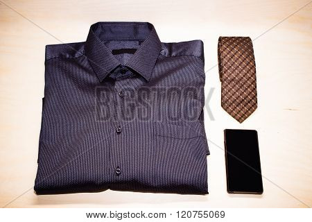 Blue shirt, smartphone and tie on wooden background