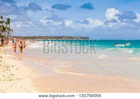 Ordinary Tourists Walk Along Beach Of Punta Cana
