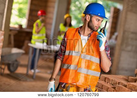 Young construction worker talking on walkie talkie at building site