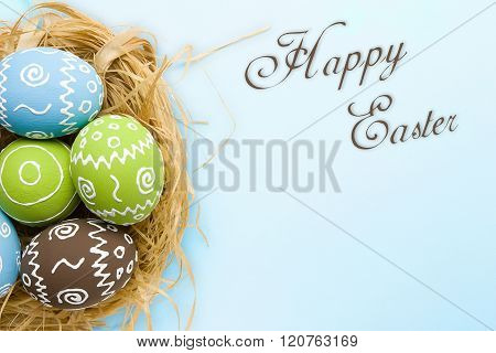 Easter card. Painted Easter eggs in nest on pale blue background