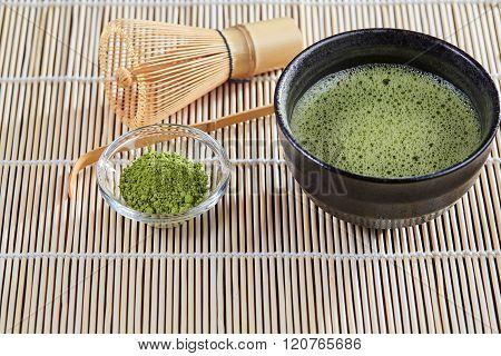 Green Matcha Tea Preparation Set On A Bamboo Table Mat