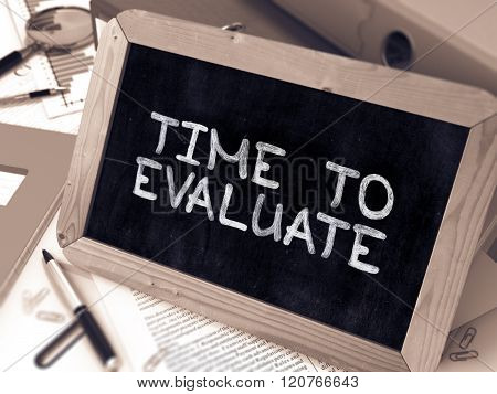 Handwritten Time to Evaluate on a Chalkboard. Composition with Chalkboard and Ring Binders, Office Supplies, Reports on Blurred Background. Toned Image. 3D Render. poster