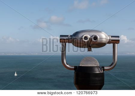 Sightseeing Binoculars Overlooking Ocean with Sailboat in Distance.