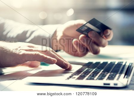 Closeup photo businessman working with notebook. Holding plastic credit card. Blurred background, film effect.