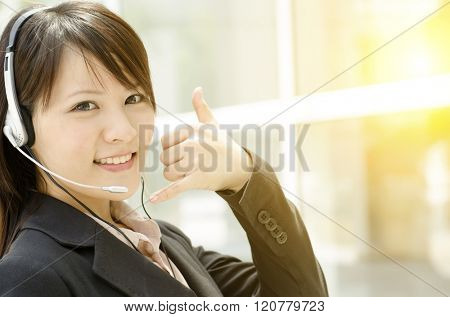 Portrait of a young Asian customer support with headset smiling, at an office environment, natural golden sunlight at background.