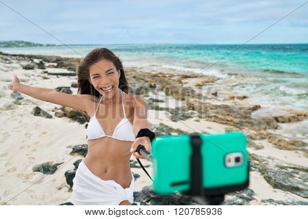 Holiday vacation girl taking smart phone self portrait pictures with selfie stick. Asian woman having fun doing mobile photography with smartphone for social media on caribbean beach summer travel.