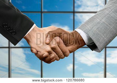 Business handshake on sky background.