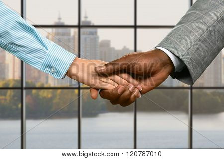 Business couple's handshake at midday.