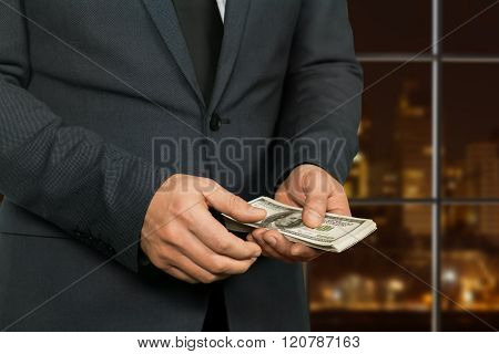 Night hotel manager counting money.