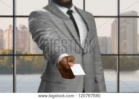 Darkskinned businessman with visit card.