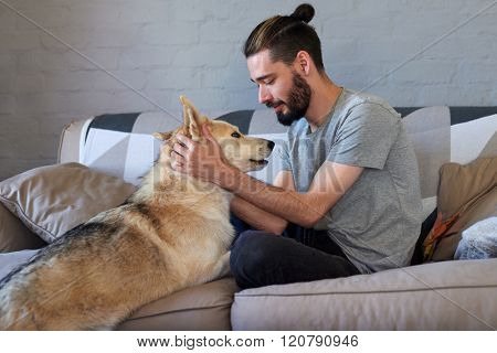 hipster man petting and rubbing his dog, loving affection relationship bond between owner and pet