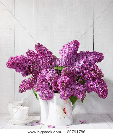 Bouquet of lilac  and cup of coffee against a white wooden board.