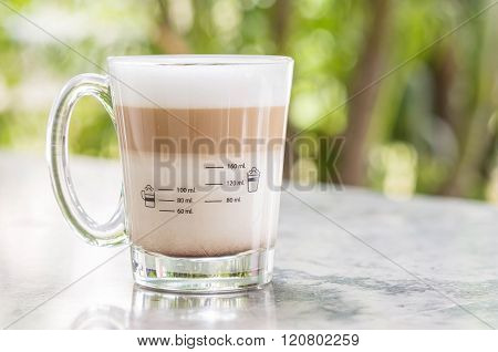 Coffee In Glass On Blurred Marble Chair And Green Tree Bokeh Background