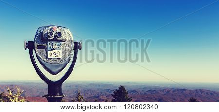 Coin-operated Binoculars Looking Out Over A Mountain Landscape