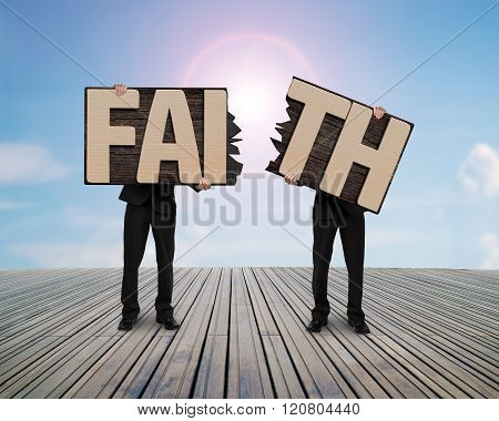Men Holding Two Cracked Faith Word Wooden Boards.