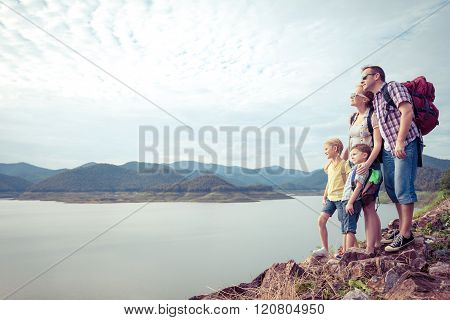 Happy Family Standing Near The Lake.