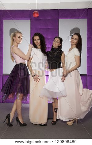 Four beautiful young adult attractive sexy and sensuality pretty girls in fashion style wearing suits, posing in full length