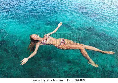 Young slim woman lie on back and relaxing in blue sea water