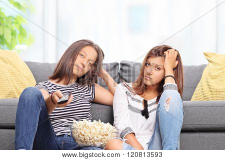 Bored teenage sisters watching TV and changing the channels isolated on white background